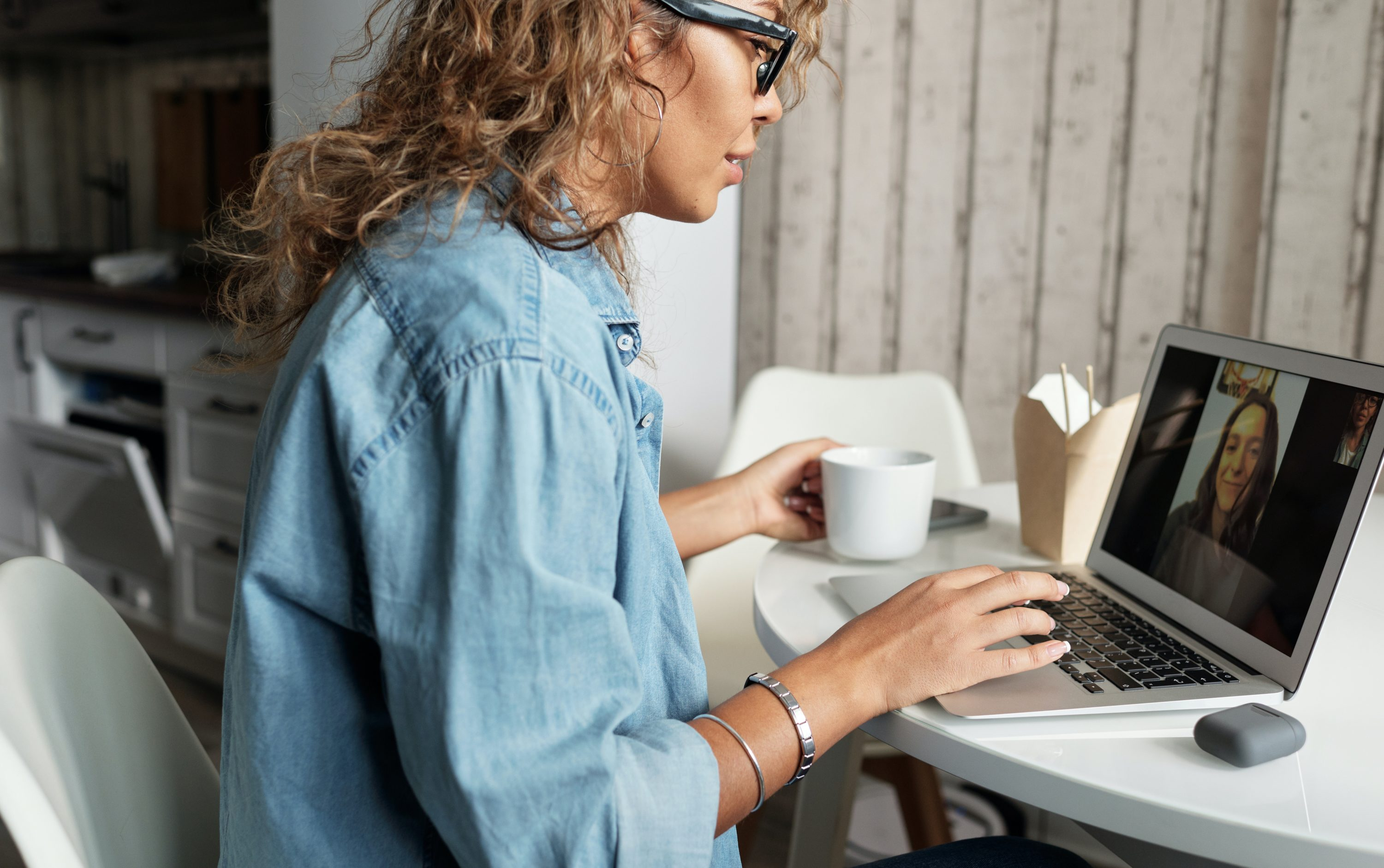 Woman with curly hair and black framed glasses sat a laptop on a call with someone